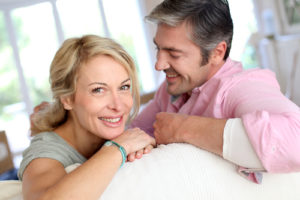 Middle aged couple relaxing in sofa at home