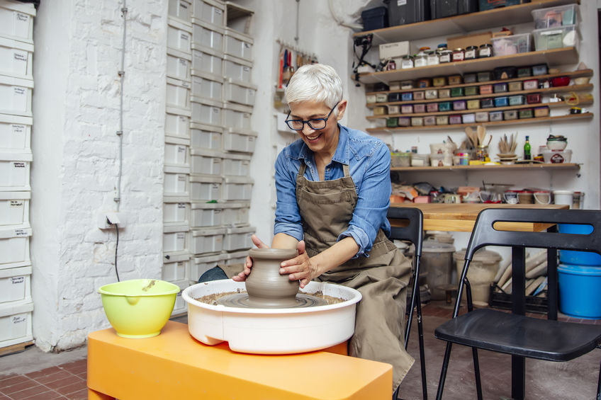 Woman potter working on pottery wheel while sitting in studio