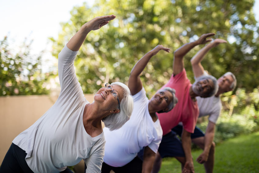 Senior people looking up while exercising with arms raised - Boron for arthritis relief