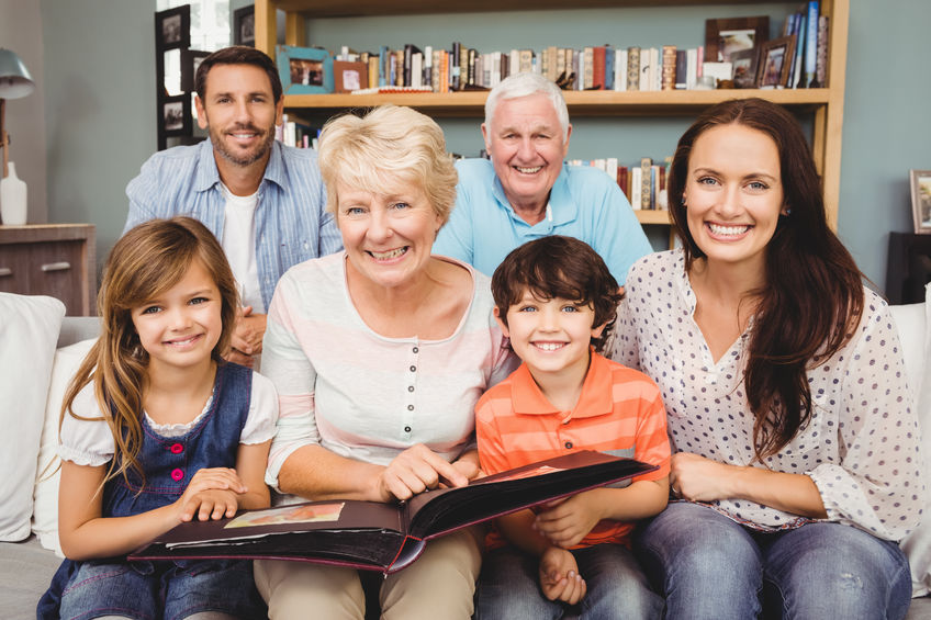 Portrait of smiling family with grandparents holding photo album at home - Experience the memory-boosting hormone called Pregnenolone