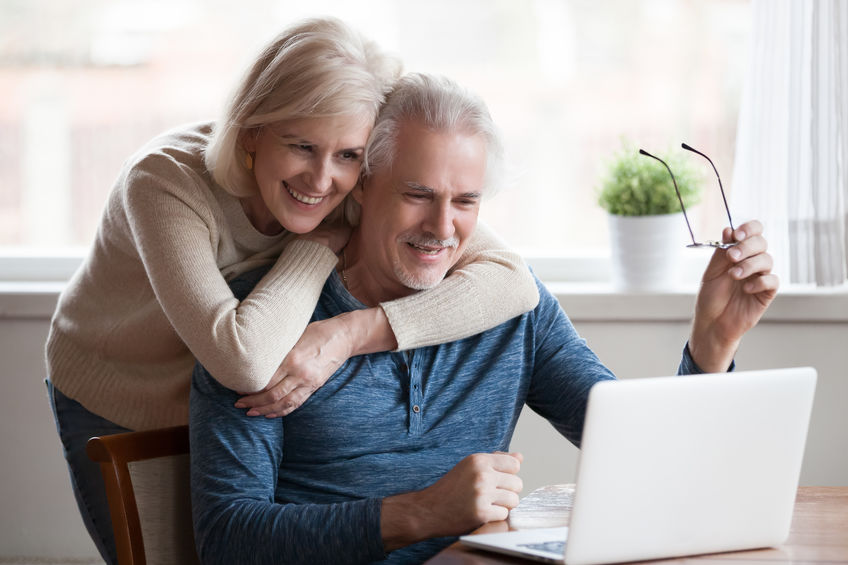 Senior middle aged happy couple embracing using laptop together - Dramatic, All-Natural Arthritis Relief: Real Experiences