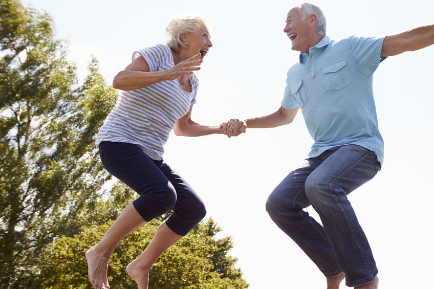 """Senior Couple Bouncing On Trampoline In Garden - A Secret Natural Remedy for """"Idling"""" Energy Levels"""
