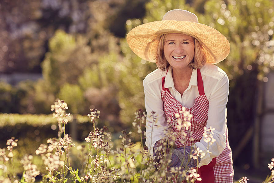 Smiling senior woman looking up from her herb garden - Naturally Boost the Body's Immune Response with DMG