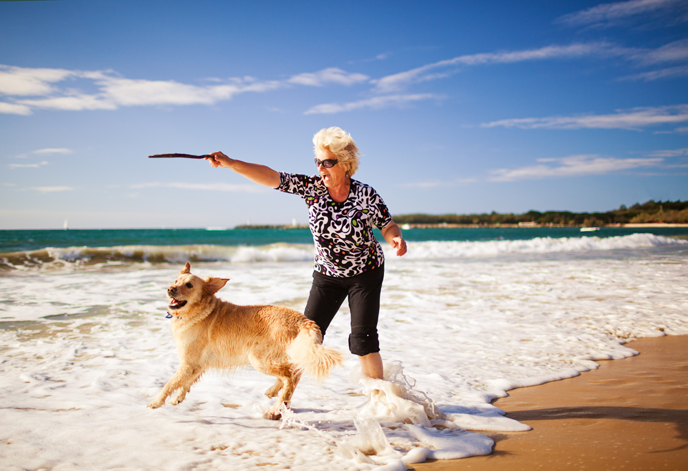 Woman playing on the beach with golden retriever - Nothing Beats D-Ribose for a Powerful Energy Boost