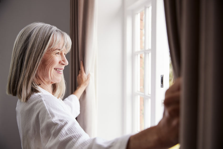 Senior Woman Opening Bedroom Curtains And Looking Out Of Window - Bounding Natural Energy, Everyday...No Coffee Needed!
