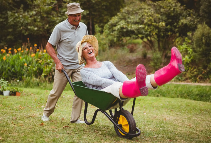 Happy senior couple playing with a wheelbarrow in a sunny day - Restore Your Youthful Vitality with 8 Key Natural Substances!