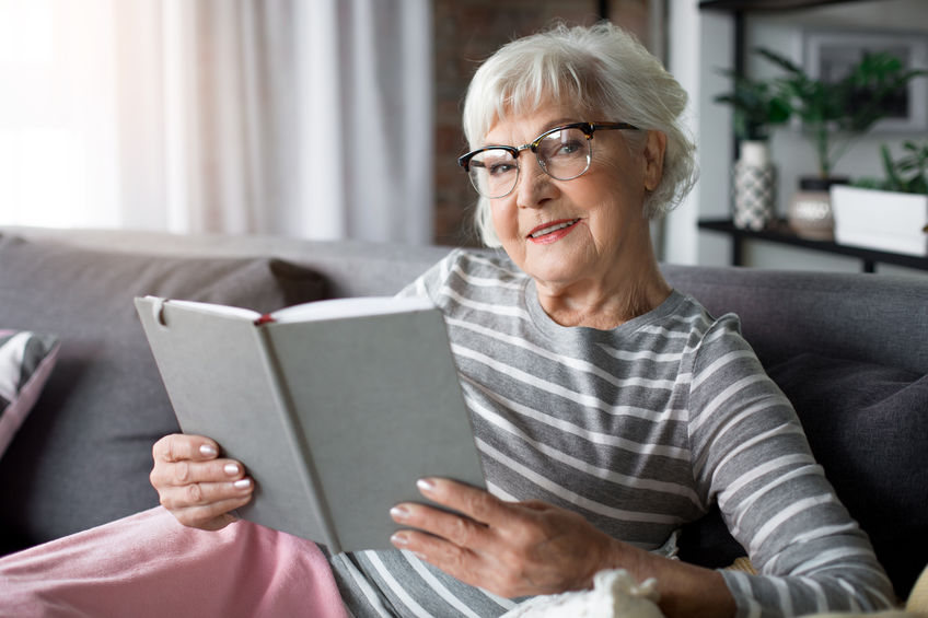 Senior lady holding book with joy - Could ATP Be Your Key to Peak Brain Performance?