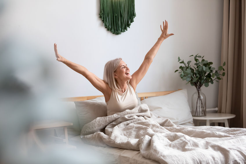 """Overjoyed pleasant middle aged woman stretching muscles - Known as nature's """"nirvana compound,"""" glucoronolactone promotes brain energy, enhanced mental clarity and mild euphoria."""