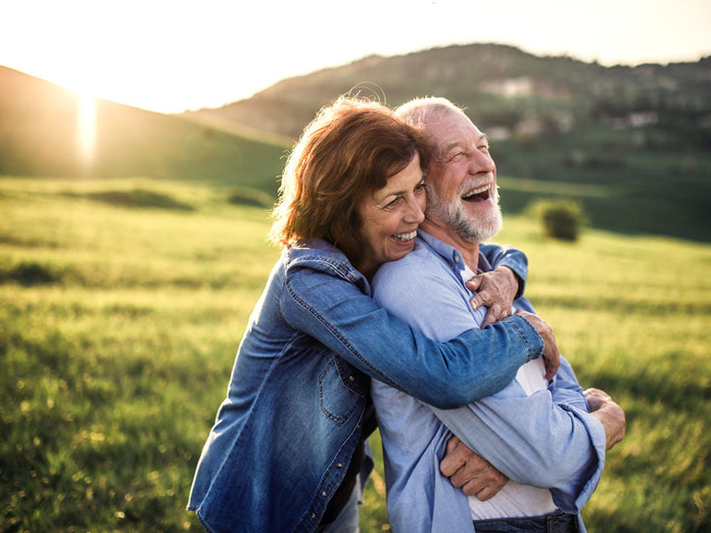Side view of senior couple hugging outside in spring nature at sunset - Take Back Your Youthful Playfulness with Maca Root!