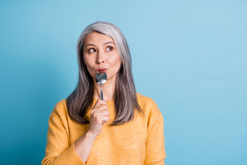 Close-up portrait photo of woman thinking, licking spoon - Could Poor Dietary Choices Affect Your Brain Function?