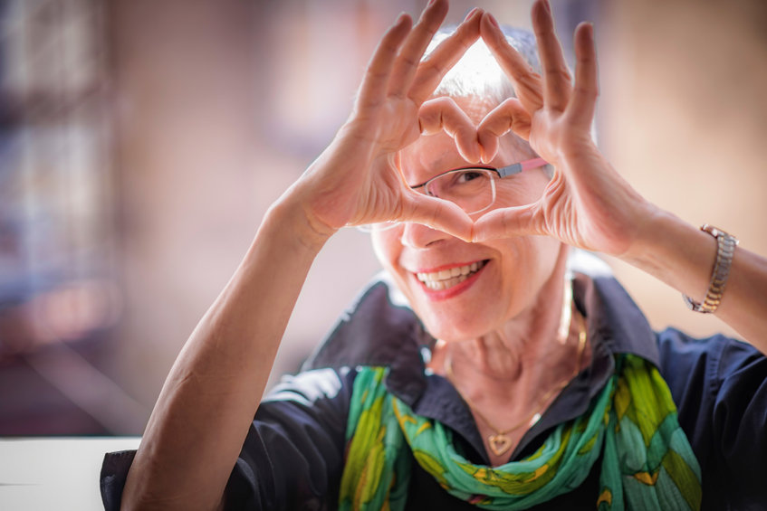 Senior woman making a heart shape - Reduce High Cholesterol and Triglyceride Levels Naturally!
