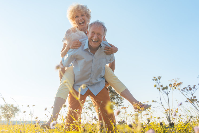Happy senior man laughing while carrying his partner on his back - Relieve Stress and Heighten Your Mood...Naturally!