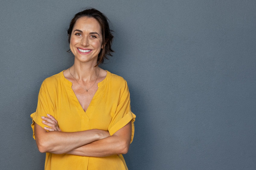 Happy mature woman smiling on grey wall - The Startling Benefits of Maca Root on Menopause Symptoms