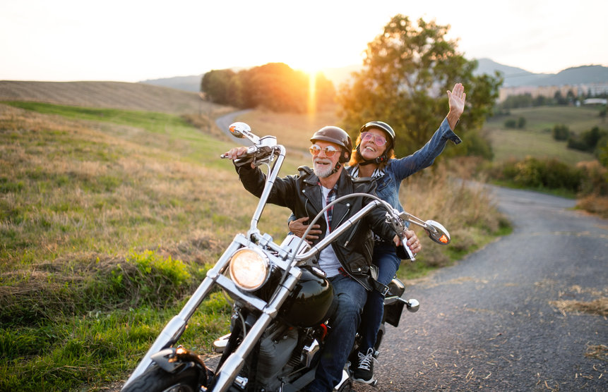 A cheerful senior couple travellers with motorbike in countryside - 8 Natural Ways You Can Boost Your Youthful Vitality and Happiness!
