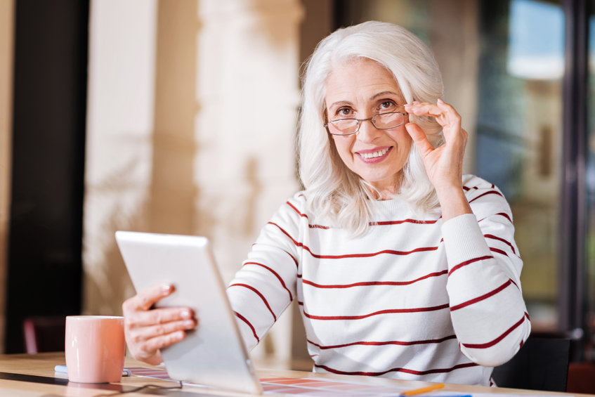 Smart, senior woman looking happy while sitting with a modern device - Help Keep Your Brain Function at its Peak...at Any Age!